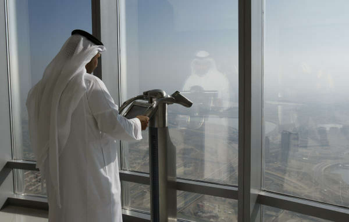 The city sprang out of the middle of the desert and is said to be one of the fastest growing cities in the world. Here an Emirati man views the city at an observation point. The Burj Dubai is home to the world's first Armani Hotel, luxury offices and residences.