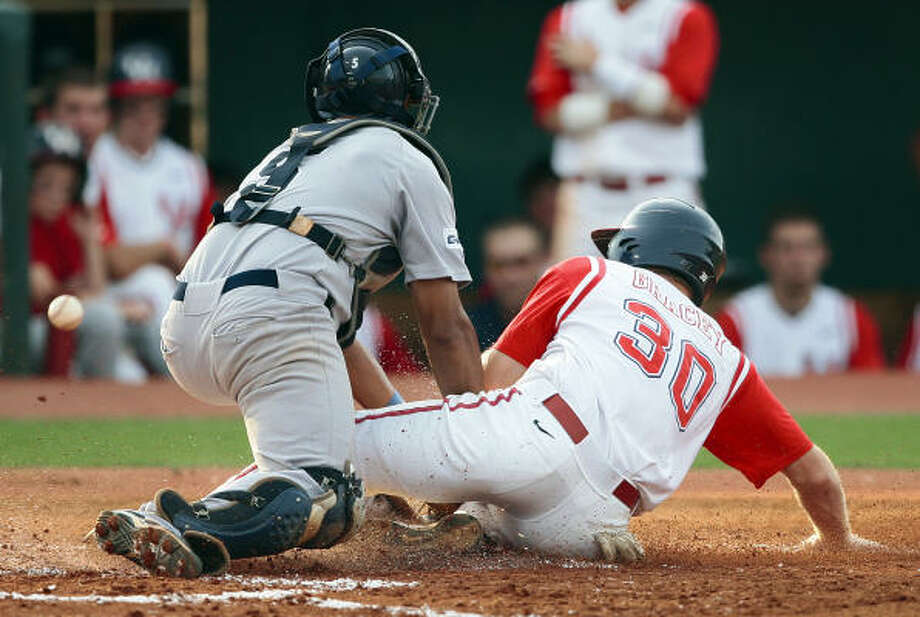 Rice catcher Diego Seastrunk can't hold onto the ball as Houston's Austin Gracey scores on a sacrifice bunt in the second inning. Photo: Bob Levey, For The Chronicle