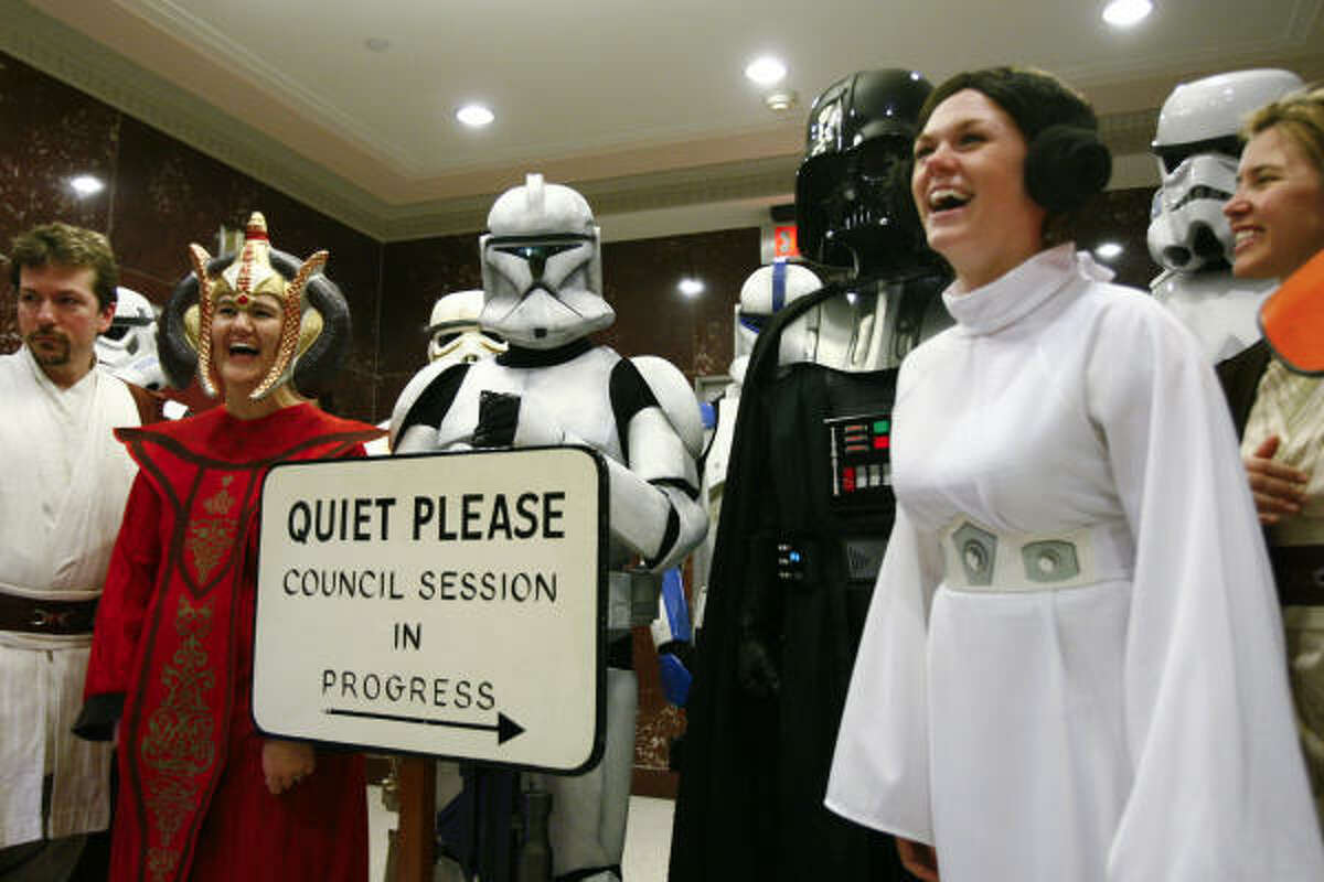 Members of the 501st Legion, an international group of Star Wars fans who own and wear realistic costumes from the Star Wars saga, share a laugh with fans outside the City Council chamber after Mayor Annise Parker declared Tuesday,