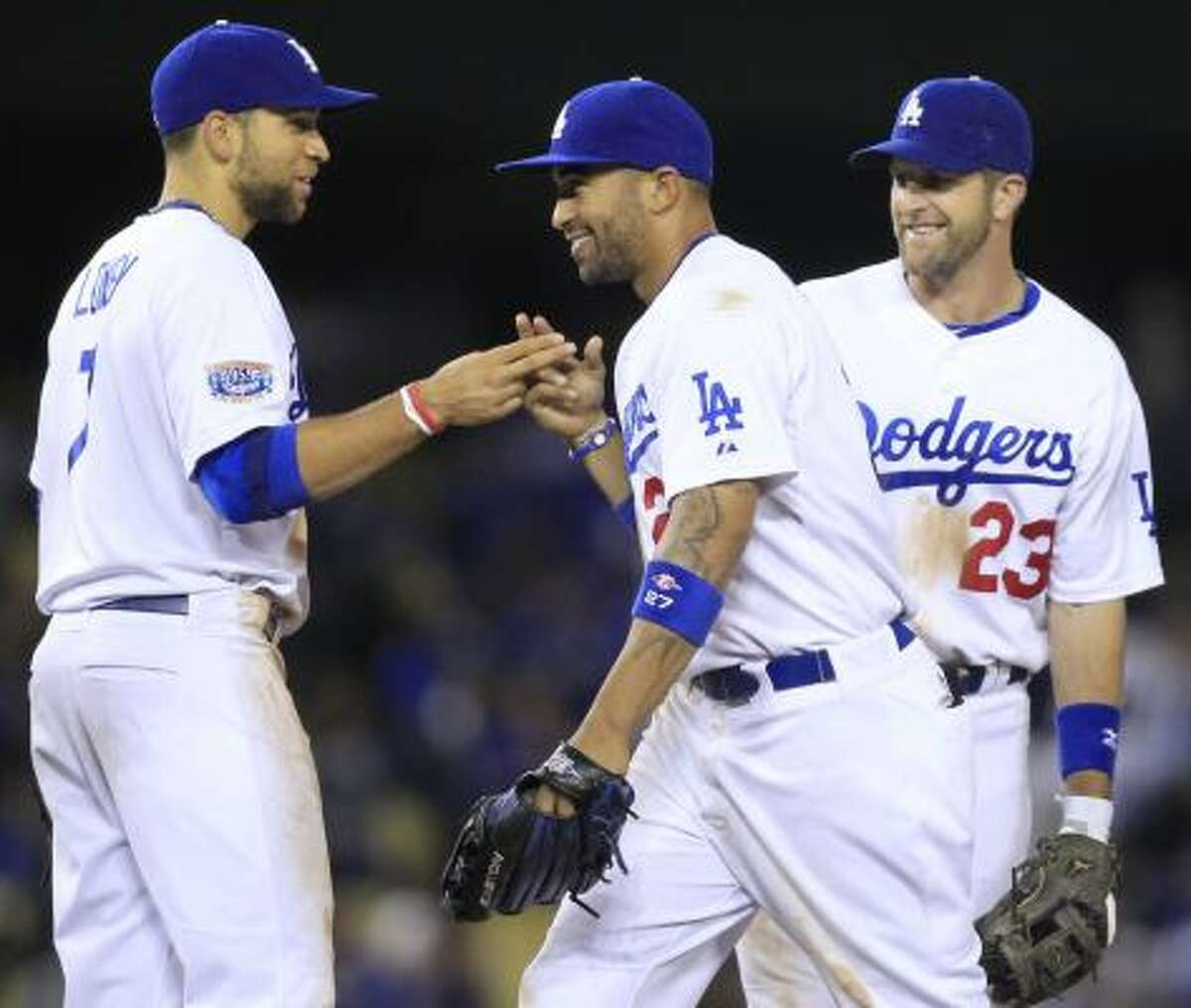 Dodgers' James Loney, left, Matt Kemp, center, and Casey Blake, right, celebrate after the Dodgers defeated the Astros 7-3.