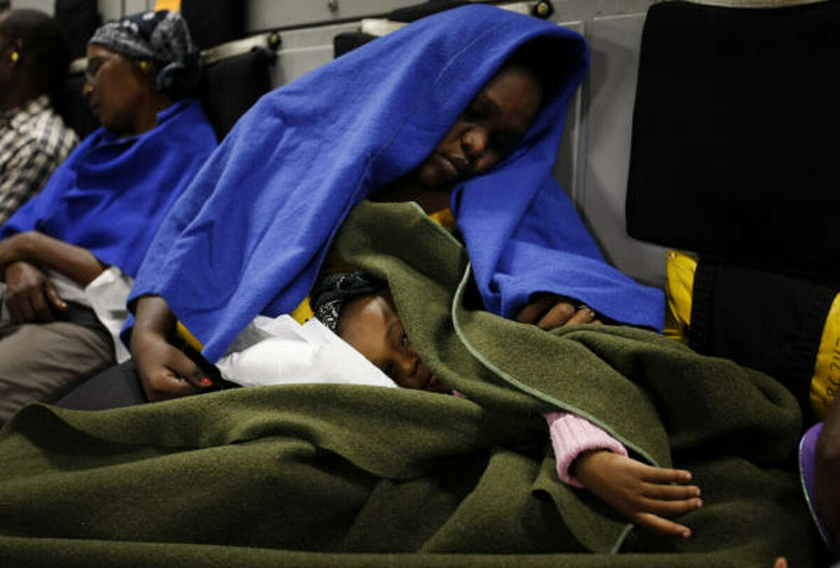 People holding U.S. passports or resident cards sleep on an Air National Guard C-17 as they are evacuated from the airport in Port Au Prince, Haiti for transport to the United States.