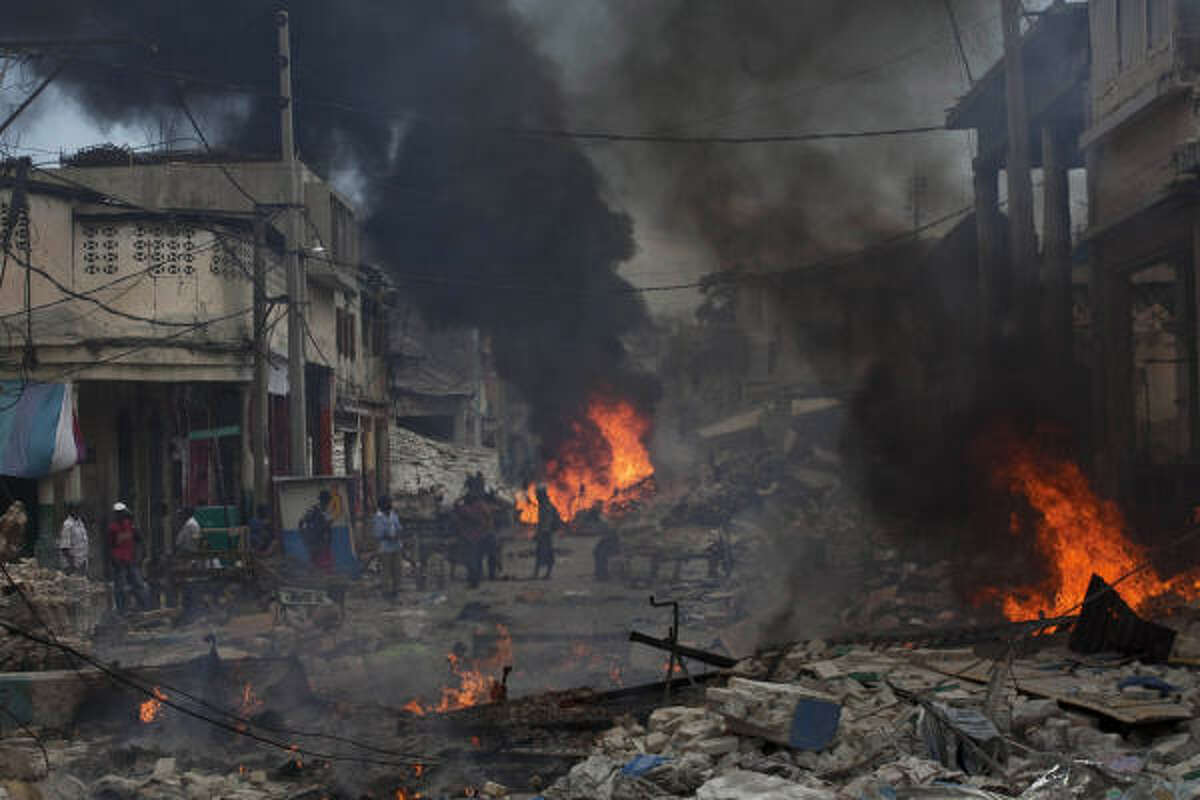 People gather among the rubble from the earthquake on a street in Port-au-Prince.
