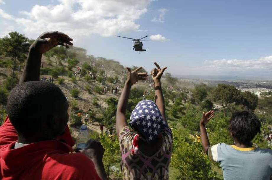 People greet a U.S. helicopter making a water drop in Port-au-Prince. Photo: Jae C. Hong, AP