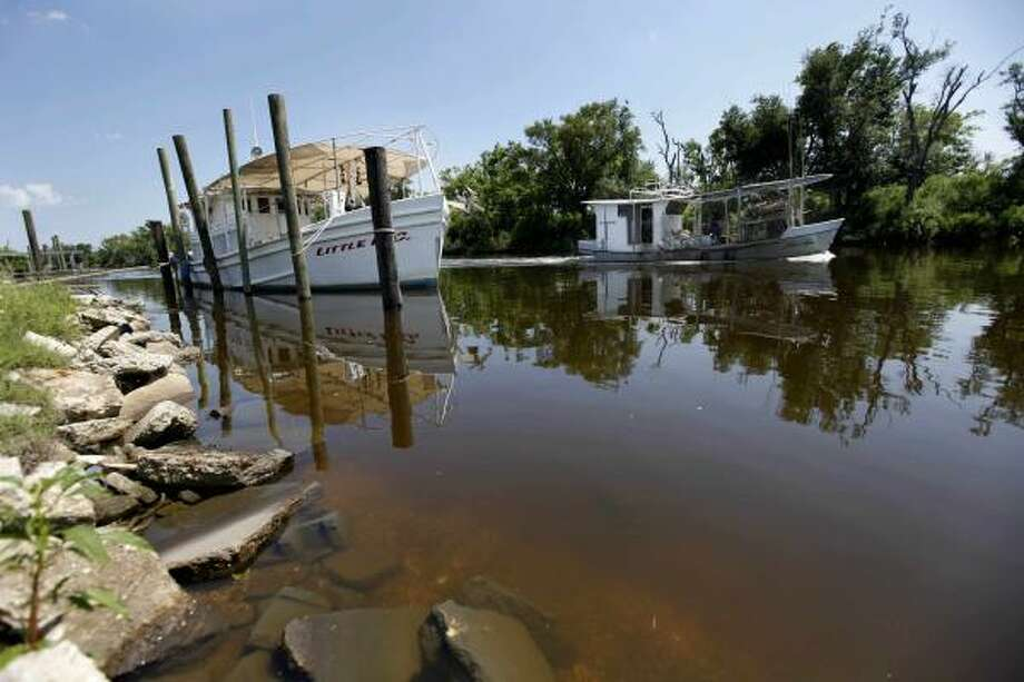 A  lone oyster boat motors down Bayou La Loutre on May 17 in Hopedale, La., near BP's oil boom deployment operations. Photo: Gerald Herbert, AP