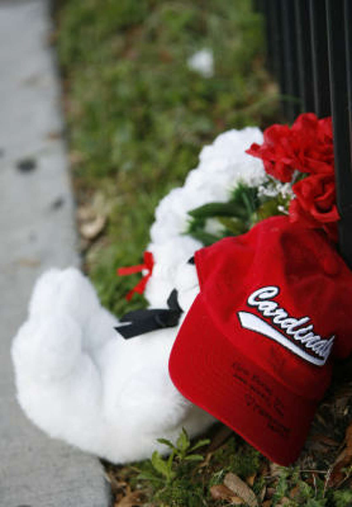 A teddy bear wearing a Bellaire High School baseball cap, sits against the fence, outside of the school, Monday, May 17, 2010, a day after Bellaire High School basketball standout Tobi Oyedeji died in a car accident early Sunday morning.