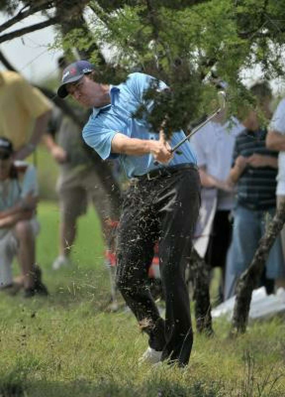 Jimmy Walker hits his second shot out of the rough on the 15th hole.