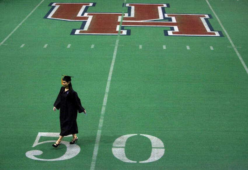 A graduate walks across the practice football field in the University of Houston Athletic and Alumni Center before attending the commencement ceremony held at Hofheinz Pavilion on the University of Houston campus.