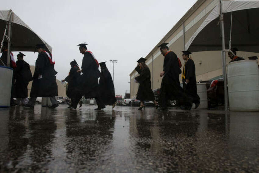 University of Houston graduates make their way to the commencement ceremony in the rain outside of Hofheinz Pavilion.