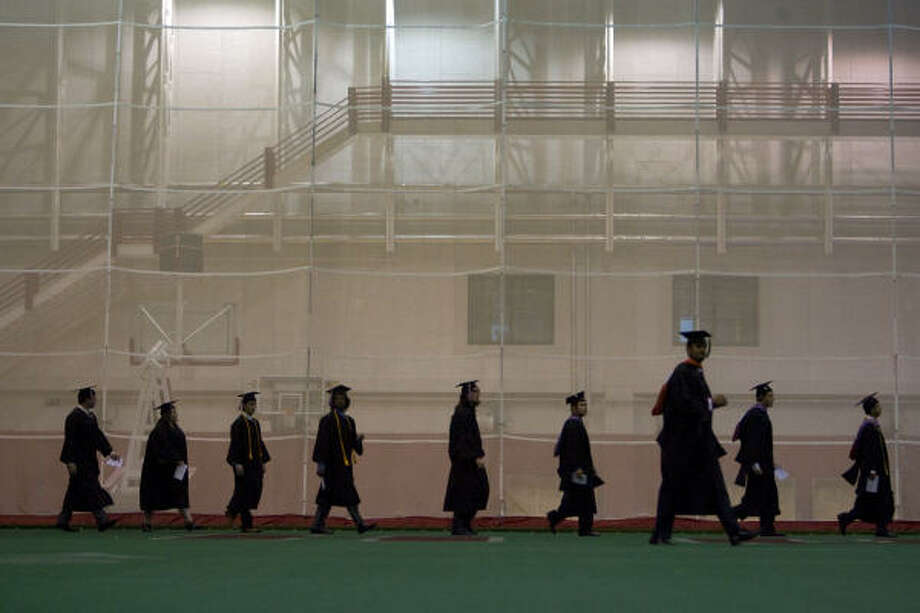 Graduates walk across the practice football field in the University of Houston Athletic and Alumni Center before attending the commencement ceremony. Photo: Johnny Hanson, Chronicle