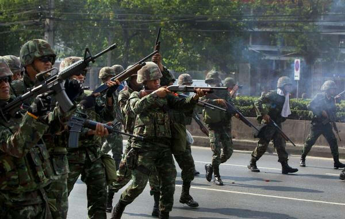 Soldiers shoot at red shirt anti-government protesters during clashes on Friday in central Bangkok, Thailand. Protesters and military clashed in central Bangkok after the government launched an operation to disperse anti-government protesters who have closed parts of the city for two months.