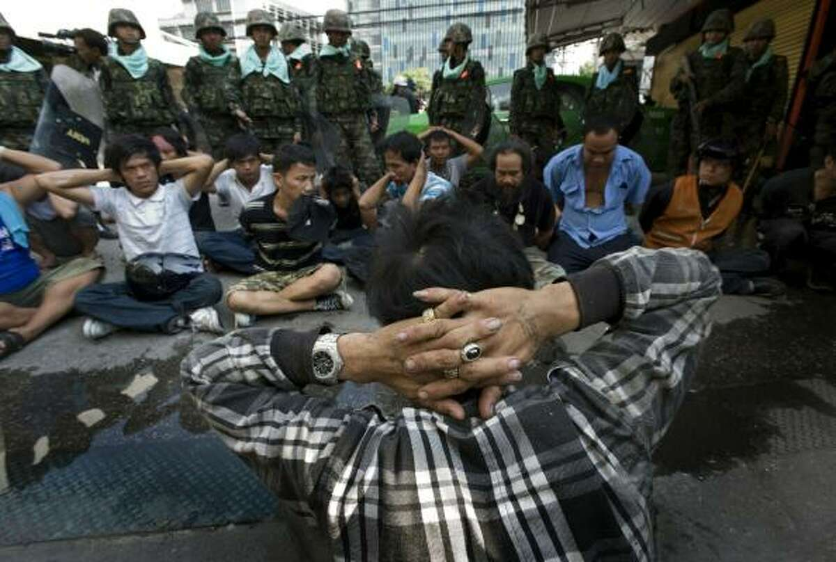 Anti-government protesters sit on the ground after being detained by Thai military forces during street clashes in Bangkok, Thailand. Protesters and military clashed in central Bangkok after the government launched an operation to disperse anti-government protesters who have closed parts of the city for two months.