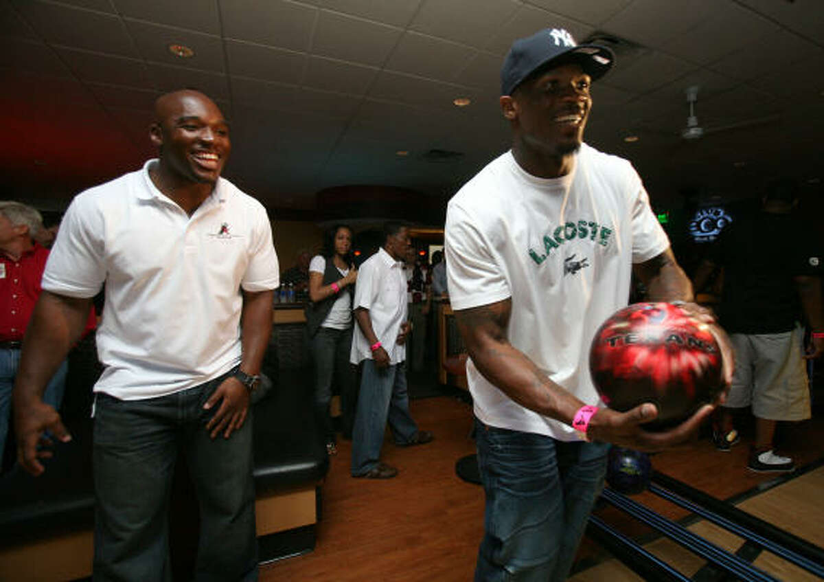 Texans linebacker DeMeco Ryans, left, cheers on his teammate wide receiver Andre Johnson during Ryans' Celebrity Bowling Blitz event.