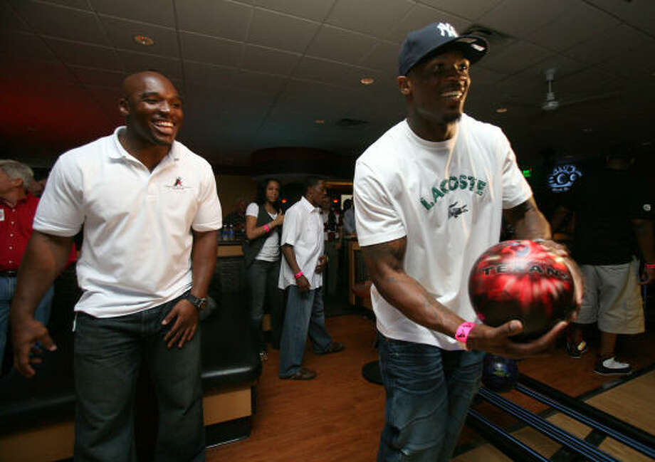 Texans linebacker DeMeco Ryans, left, cheers on his teammate wide receiver Andre Johnson during Ryans' Celebrity Bowling Blitz event. Photo: Johnny Hanson, Chronicle