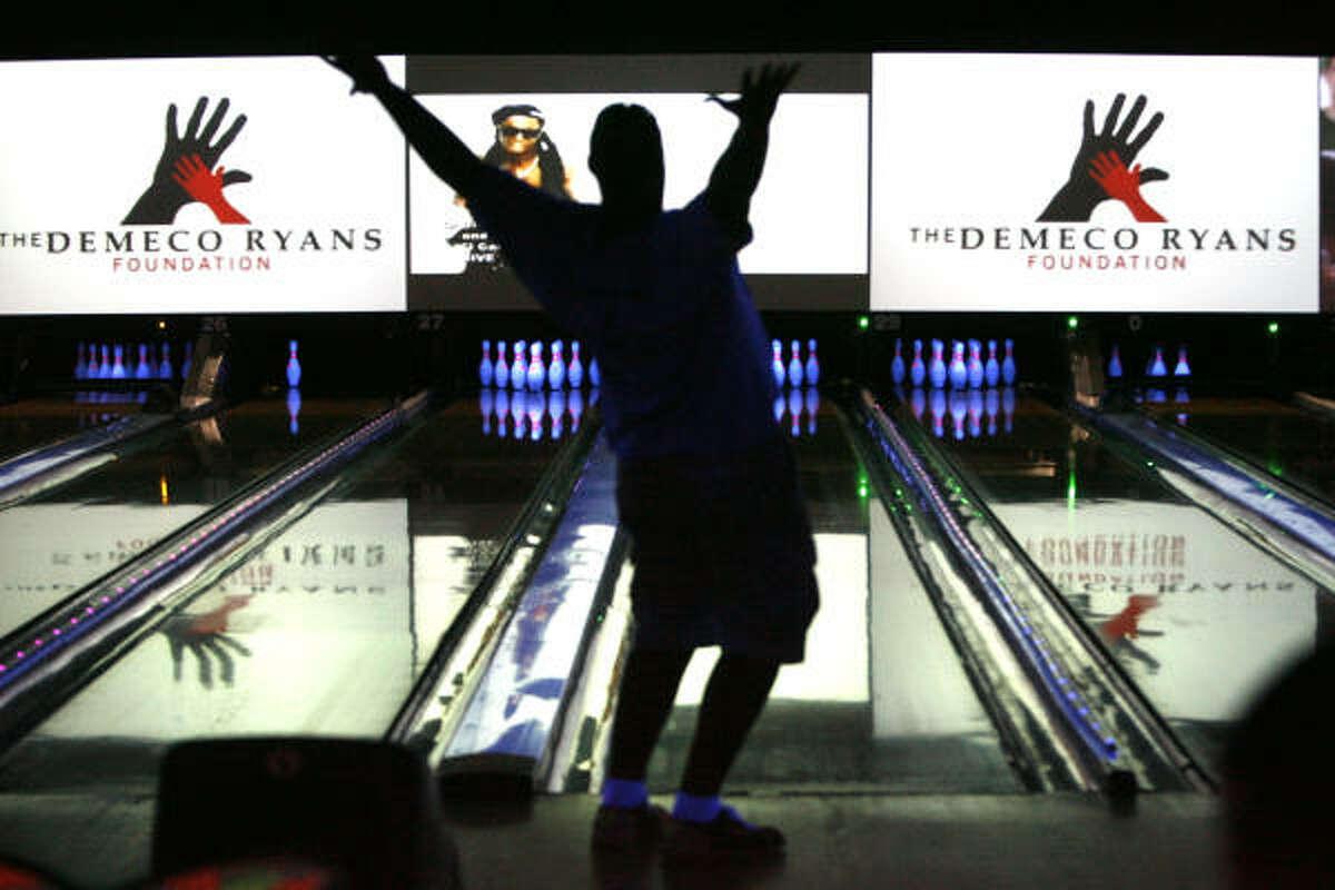 Texans' Adam Stenavich celebrates scoring a strike during his teammate, Demeco Ryans' Celebrity Bowling Blitz.