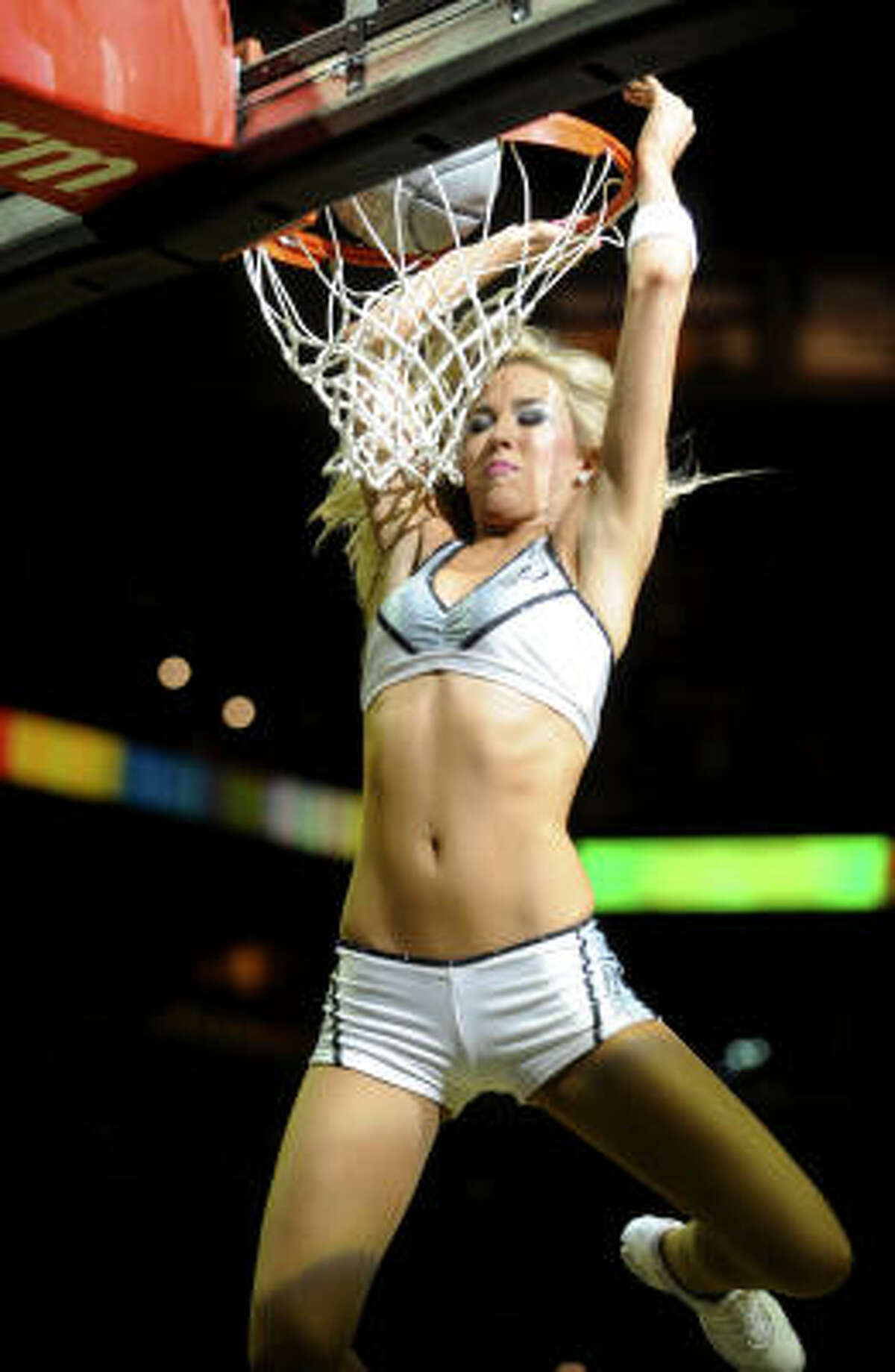A San Antonio Spurs Silver Dancer dunks during a timeout at the AT&T Center on Wednesday, March 31, as the Spurs take on the Rockets.