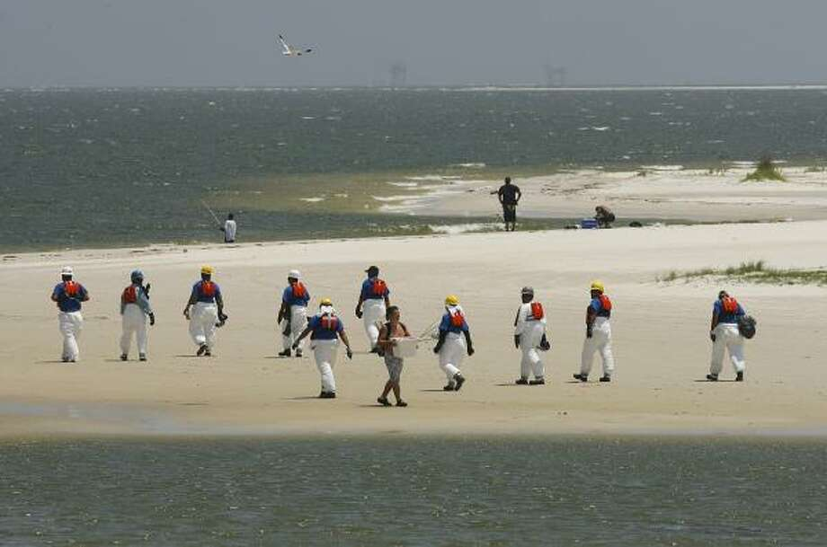 Workers in protective suits scour the public beach and Sand Island for tar balls Wednesday, May 12, 2010, in Dauphin Island, Ala. Photo: MIKE KITTRELL, AP