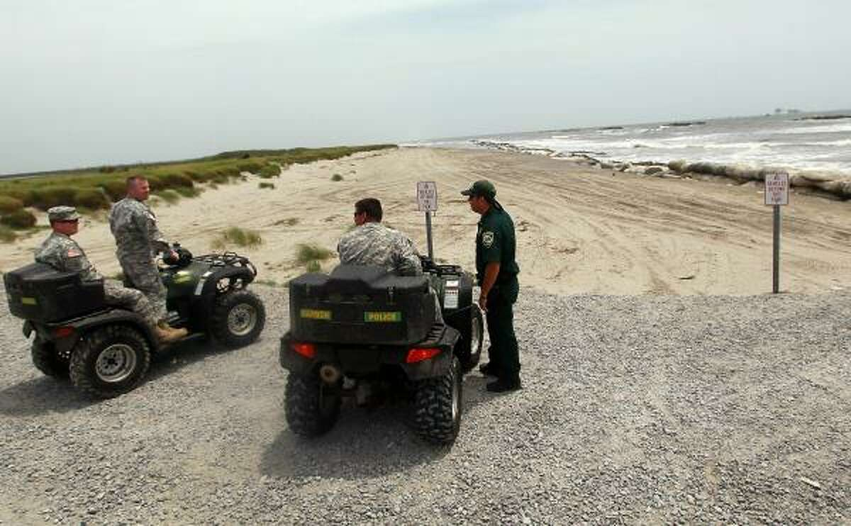Louisiana National Guard and a police officer gather next to the beach where what appears to be small oil globs have washed ashore at Fourchon Beach as efforts continue to contain BP's massive oil spill on May 13, 2010 in Lafourche Parish, La.