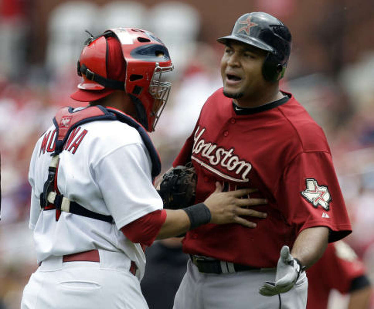 The Astros' Carlos Lee, right, is held back by St. Louis catcher Yadier Molina. Lee was yelling at Cardinals starting pitcher Chris Carpenter during the third inning after Lee popped out.