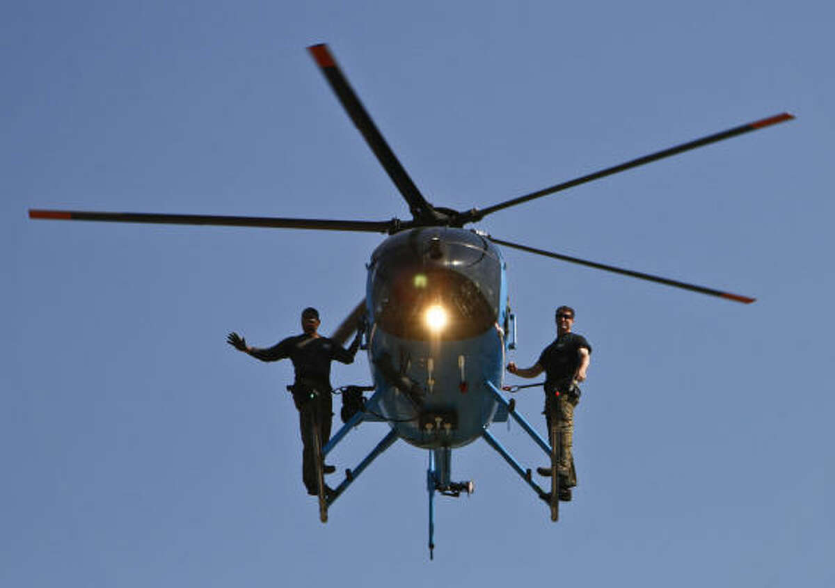 Members of the Houston SWAT team ride on a helicopter during a presentation for Houston-area school students. During these prescheduled tours, children will meet with officers and partake in demonstrations from the Air Support Division, K-9 Unit, SWAT, the Dive Team, and the Community Services Unit. It is during Police Week that the community remembers and honors those who have given the ultimate sacrifice of their lives so that the public can live in safety and peace.