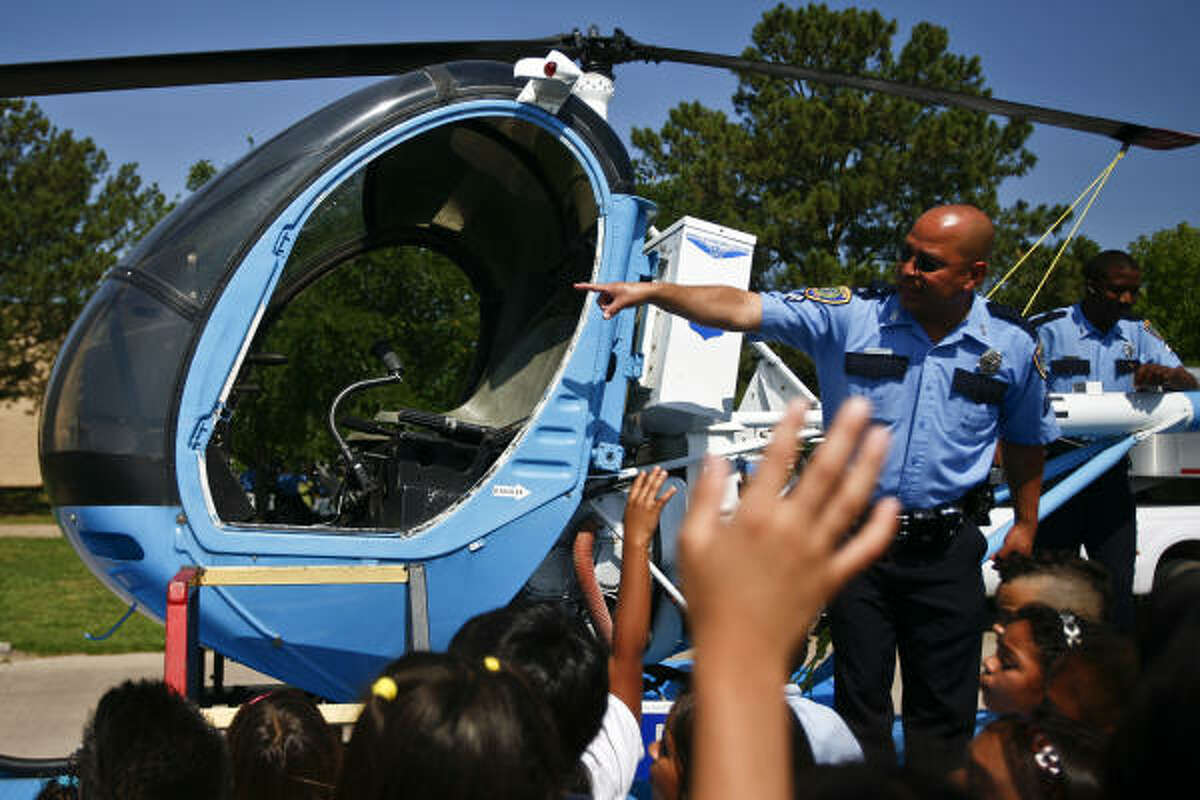 Oficer Anthony Valle talks about the 300c police helicopter to Houston-area school students as they get an inside look at various aspects of HPD put on by members of the Houston Police Department's Training Division at the L. D. Morrison Police Training Academy during Police Week in Houston. An estimated 4200 students will attend the event over the course of the week. During these prescheduled tours, children will meet with officers and partake in demonstrations from the Air Support Division, K-9 Unit, SWAT, the Dive Team, and the Community Services Unit.