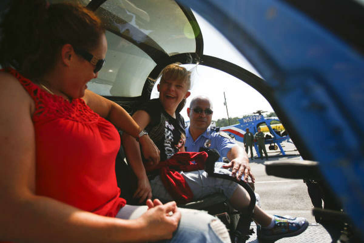 Oficer Anthony Valle helps Taylor Hendrix, 13, sit in the cockpit of a police helicopter as Jean Schubert looks on as Houston-area school students get an inside look at various aspects of HPD put on by members of the Houston Police Department's Training Division at the L. D. Morrison Police Training Academy during Police Week.