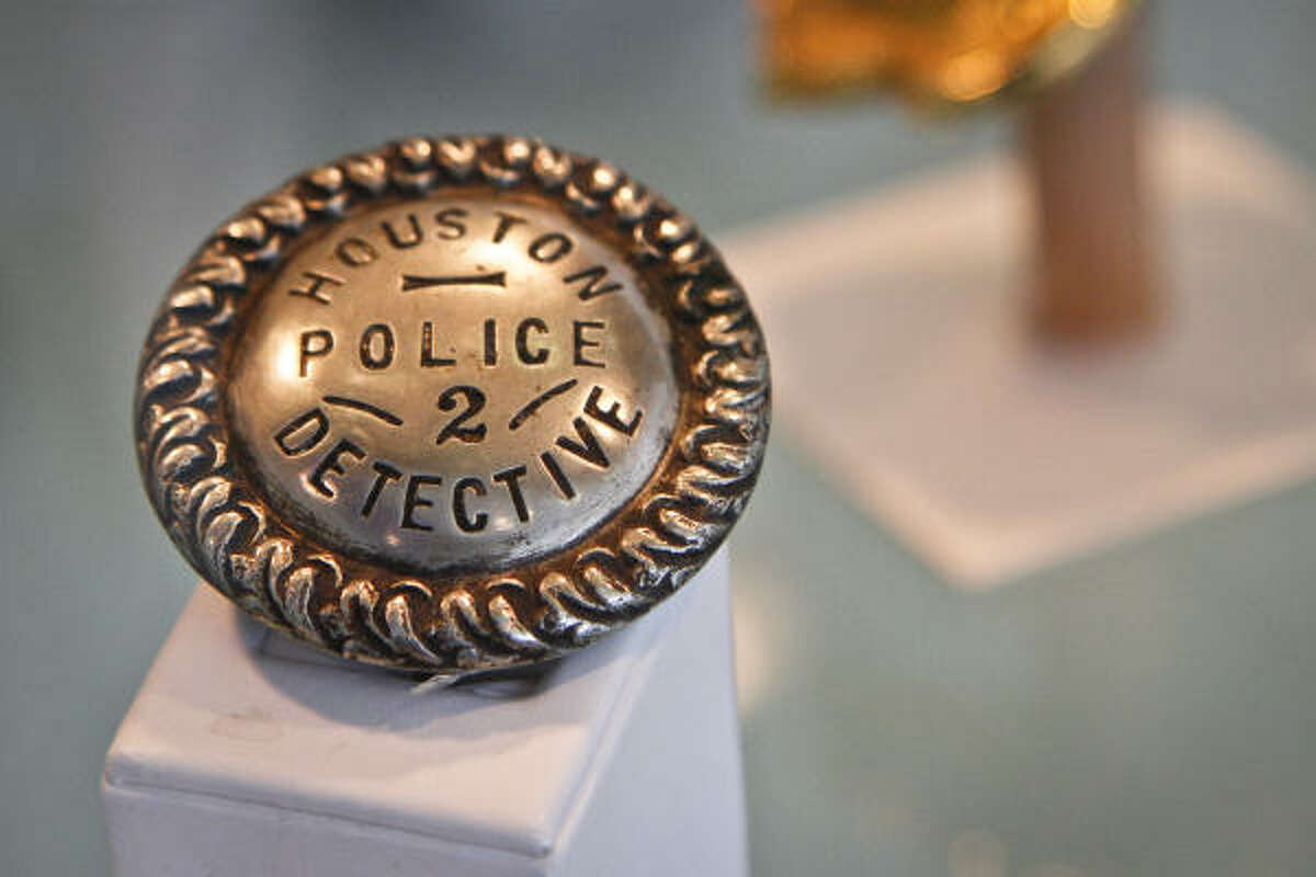 A Houston Police Department detective badge from 1915-1917 is on display at the grand opening ceremony for the HPD Museum and Officers' Memorial in the lobby of the HPD Headquarters.