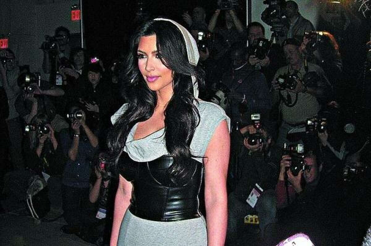 Kim Kardashian wears her own design: a jersey hooded dress teamed with a leather corset. She has a line with Bebe.