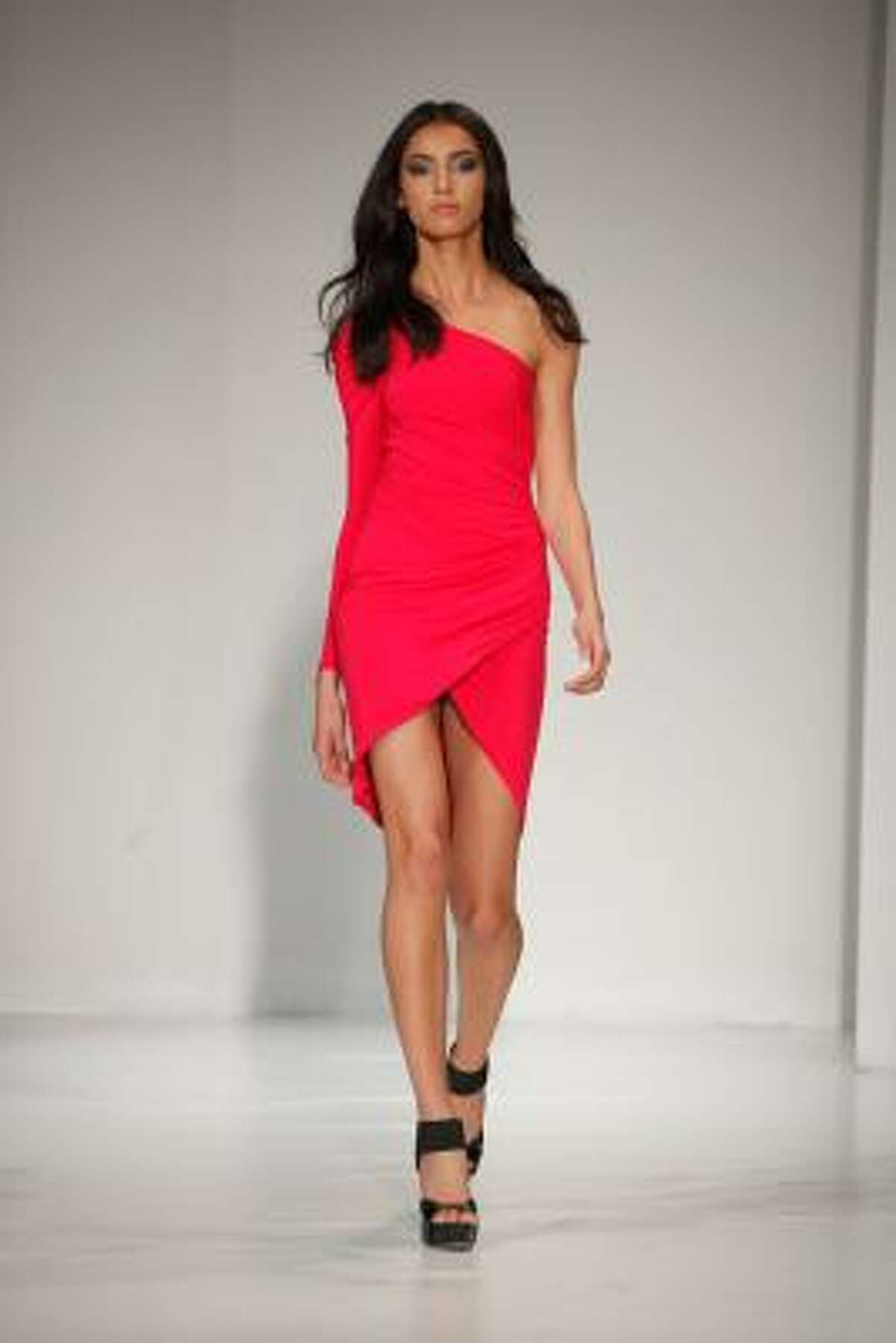 An asymmetrical one shoulder red ruched dress.