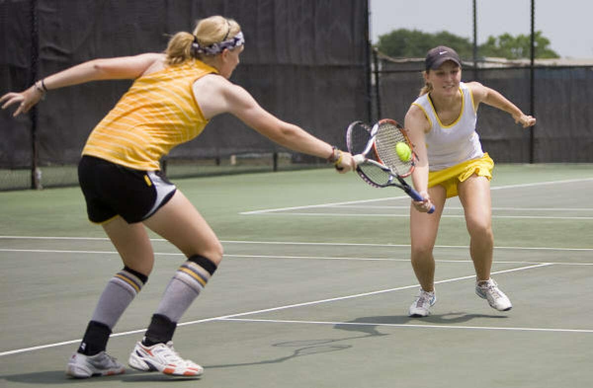 Melissa and Allison Burckhartt from Klein Oak High School return a ball from Klein High School players.