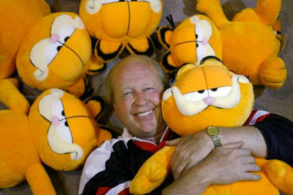 Jim Davis hugs a stuffed version of his cartoon creation, Garfield the Cat. •   Share your cat pics.