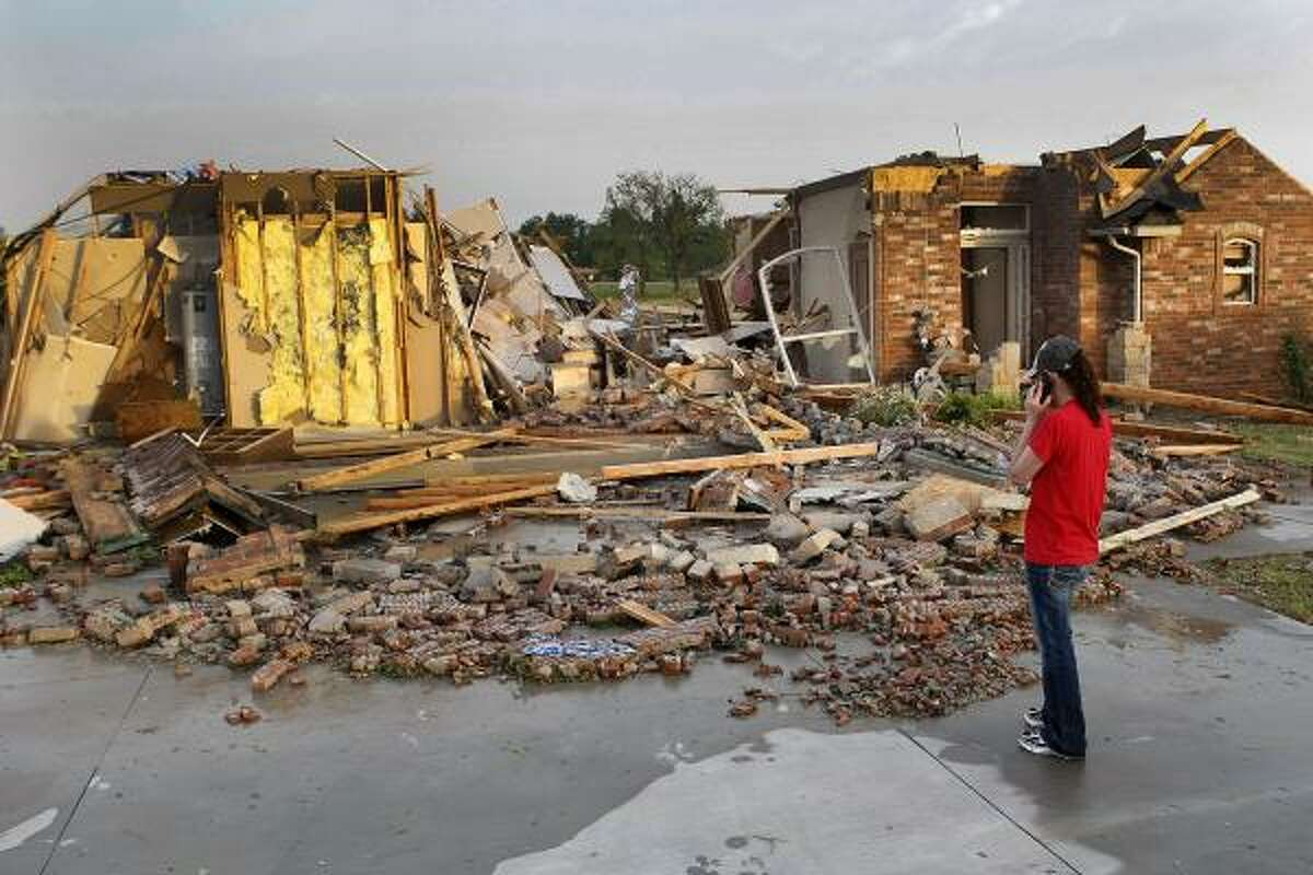 In this Monday, May 10, 2010 photo, Ann Powell calls her insurance company while standing in front of what is left of her house at 306 Mounds after tornadoes ripped through Harrah, Okla. Powell moved to Oklahoma about a year ago from California.