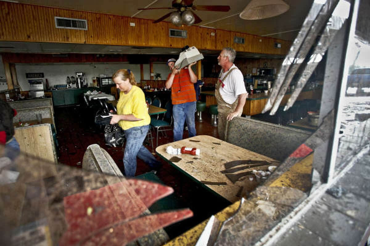 In this Monday, May 10, 2010 photo, employees gather valuables from inside the Anderson Travel Plaza after a tornado hit Oklahoma City, Okla. Emergency authorities in Oklahoma City urged residents to stay off the roads in affected areas Tuesday to allow rescue workers to search for survivors among the wreckage of their homes.