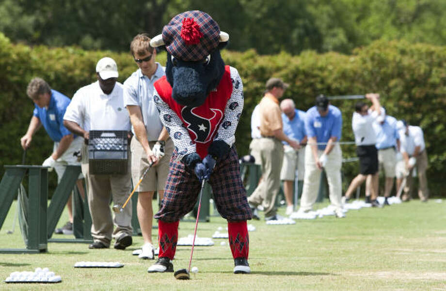Texans mascot Toro lines up a shot on the driving range. Photo: Brett Coomer, Chronicle