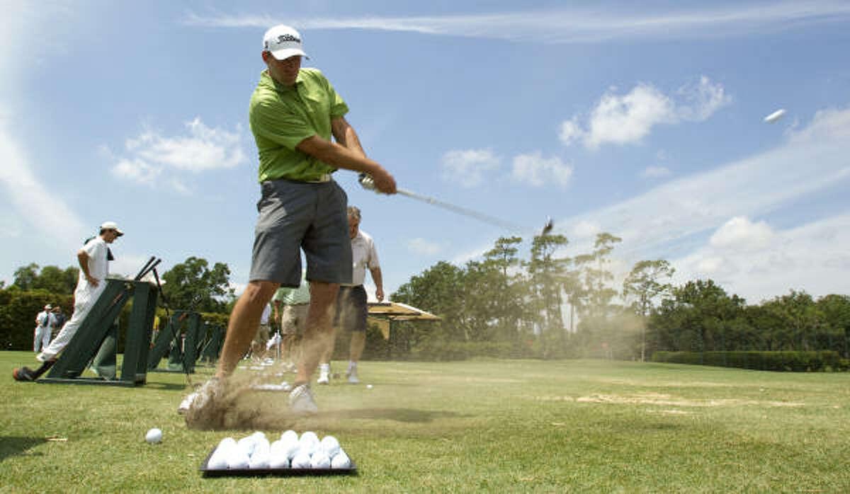 Texans quarterback Matt Schaub hits a golf ball on the driving range.