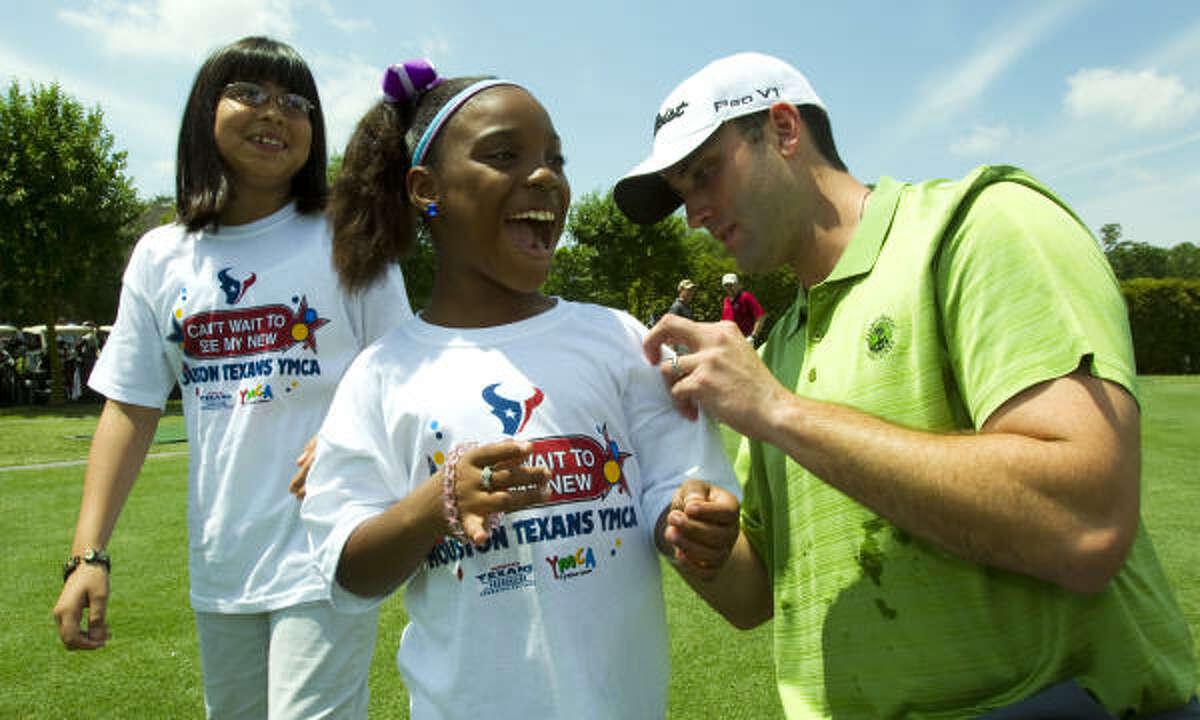 Texans quarterback Matt Schaub autographs L'layah Parker's t-shirt, while Emily Lopez watches before the Texans Celebrity Golf Classic.