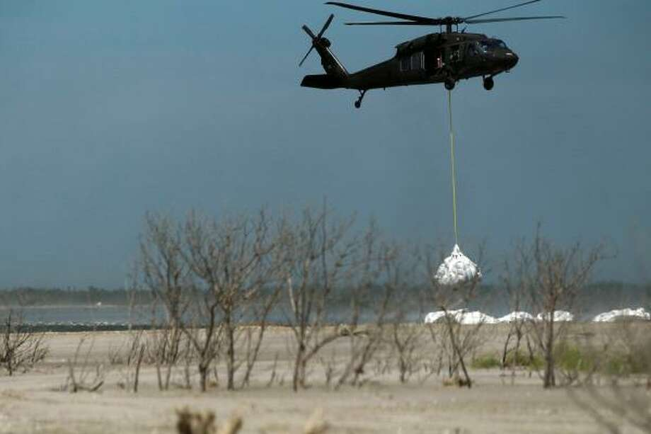 A Louisiana National Guard helicopter airlifts sling load sand bags into place as they create a barrier in an attempt to protect an estuary from the massive oil spill on May 10, 2010 in Lafourche Parish, La. Photo: Joe Raedle, Getty Images