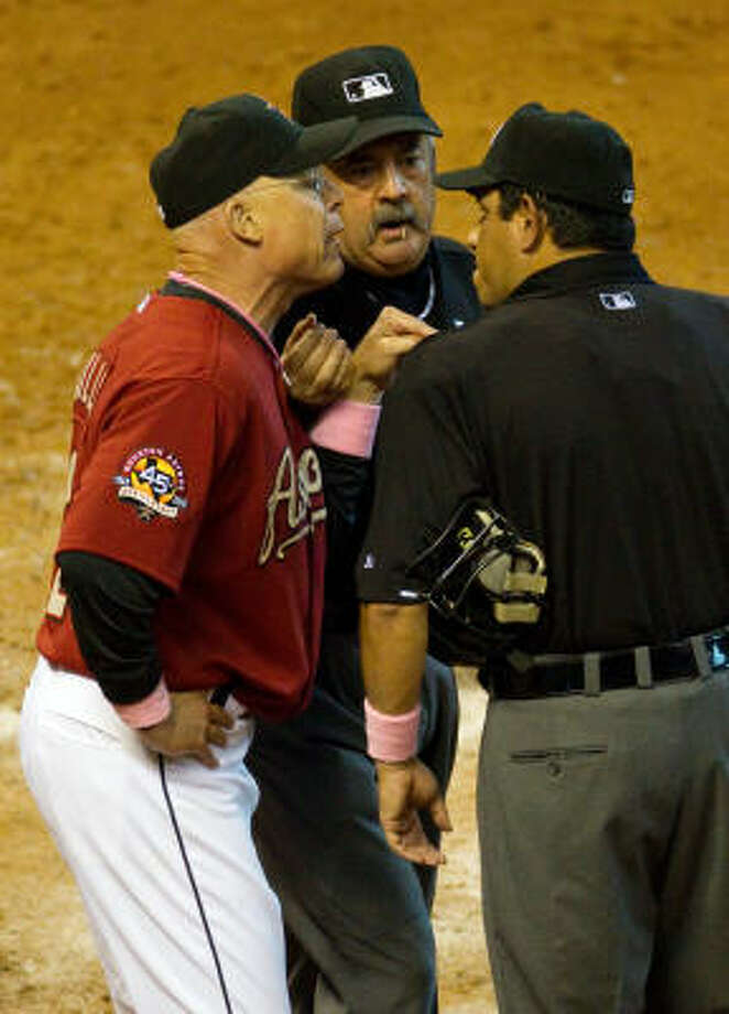 Umpire Tim Tschida steps in to separate Astros manager Brad Mills from home plate umpire Alfonso Marquez. Mills was ejected for the first time in his short tenure with the Astros for arguing balls and strikes. Photo: Smiley N. Pool, Chronicle