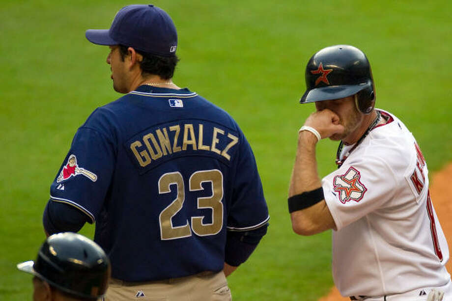 Astros shortstop Jeff Keppinger gestures to the dugout with a motion suggesting a punch to the nose after hitting a single in the fourth inning, as Padres first baseman Adrian Gonzalez stares off into the distance. Photo: Smiley N. Pool, Chronicle