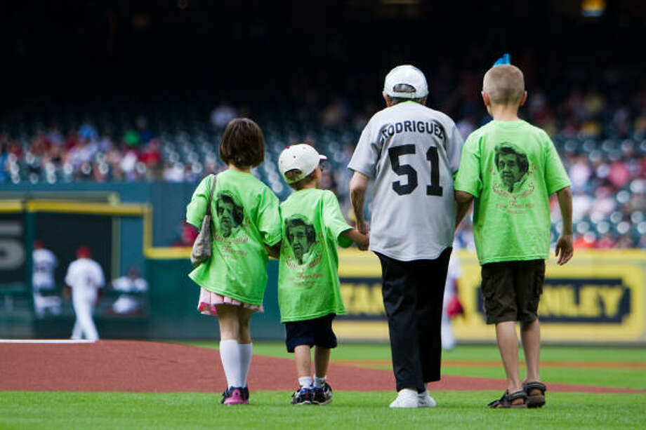 Francis Senak is accompanied by three great-grandchildren as she heads to the mound to throw out the first pitch before Saturday's game. Saturday marked Senak's 80th birthday. Photo: Smiley N. Pool, Chronicle