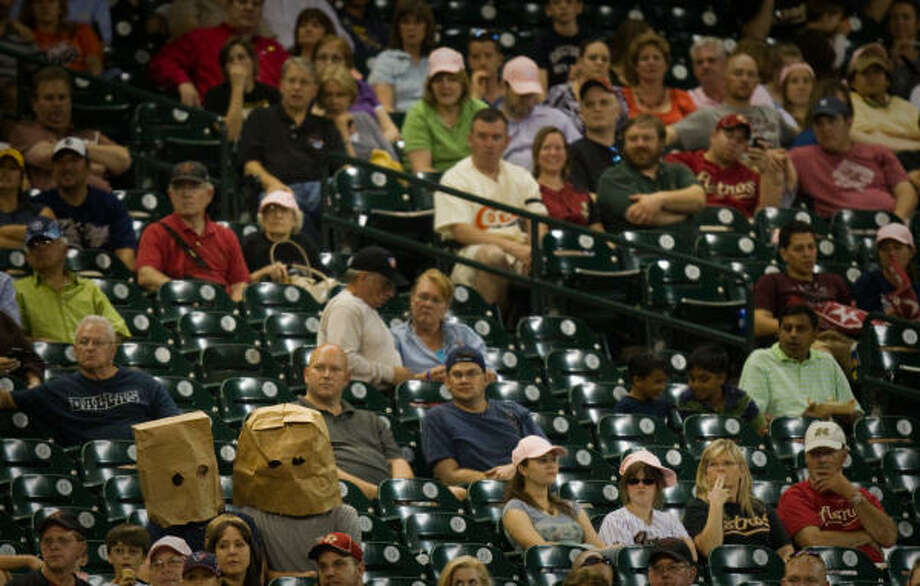 Two Astros fans cover their heads with paper bags as they look on in the ninth inning. Photo: Smiley N. Pool, Chronicle