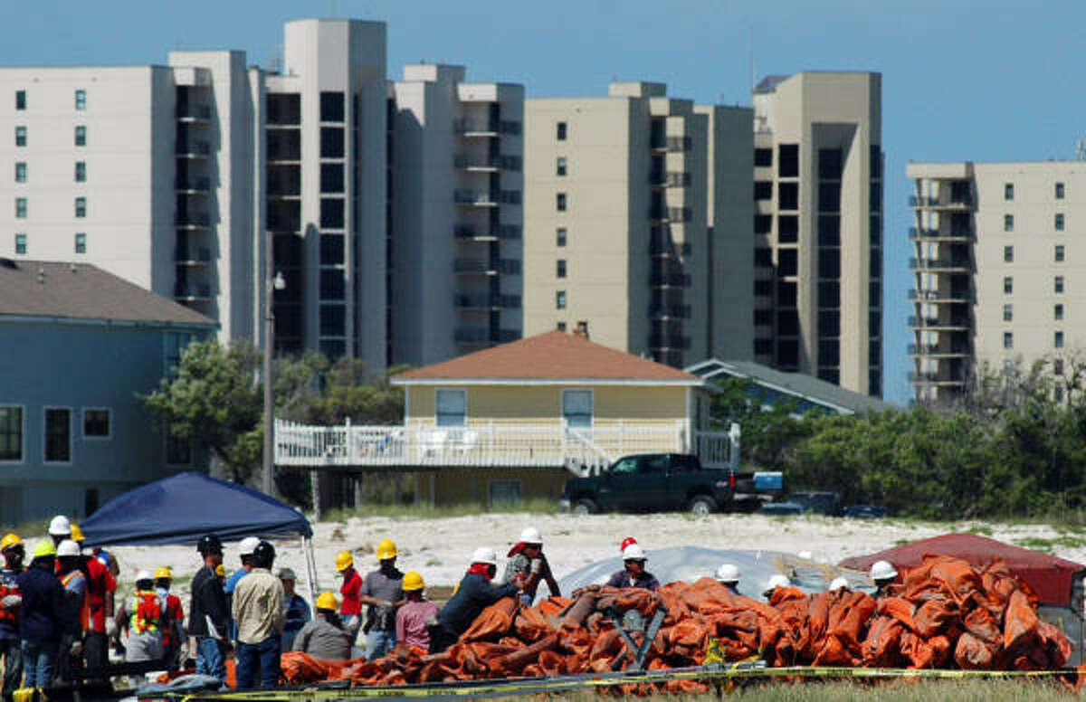 Workers handle oil-blocking booms Sunday in a condo parking lot in Orange Beach, Ala.