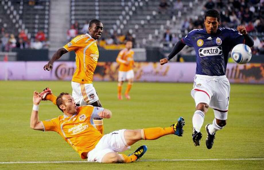 Dynamo midfielder Brad Davis, left, kicks the ball past Chivas USA's Dario Delgado to score a goal during the first half of Saturday's game in Carson, Calif. The Dynamo won 2-0. Photo: Kevork Djansezian, Getty Images