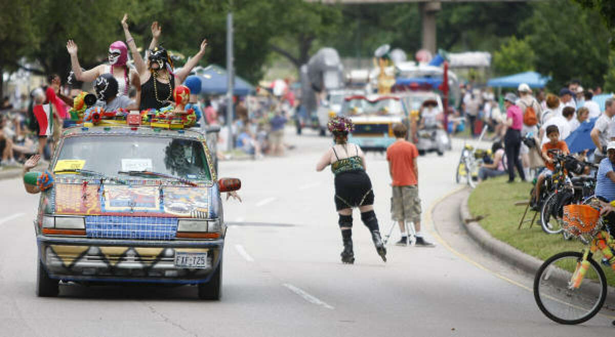 The 'Lucha Mobile' art car and it's masked participants wave to the crowds that line Allen Parkway.