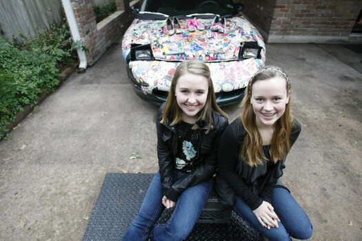 Grace Palmer, left, and Lindsey Taylor, both freshmen at Memorial High School, sit in front of their first art car. It's a tribute to fashion, using magazine clippings and accessories like shoes and nail polish. Photo: Nick De La Torre, Chronicle
