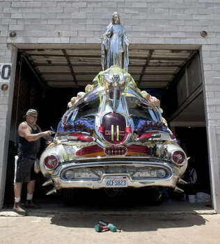 Jack Haye, of Petaluma, Ca., adds beads and tubes of plastic to the art car 'DC-39.' Photo: Nick De La Torre, Chronicle