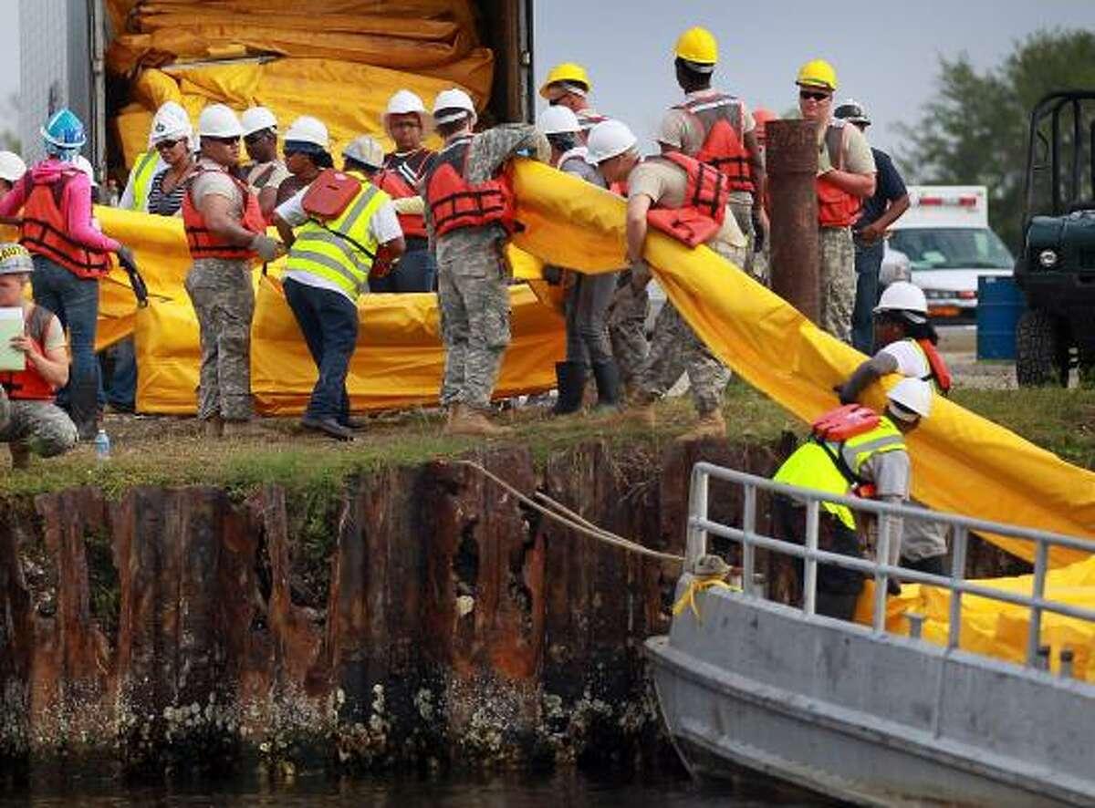 Workers load oil booms onto a boat Saturday near Shell Beach, La.