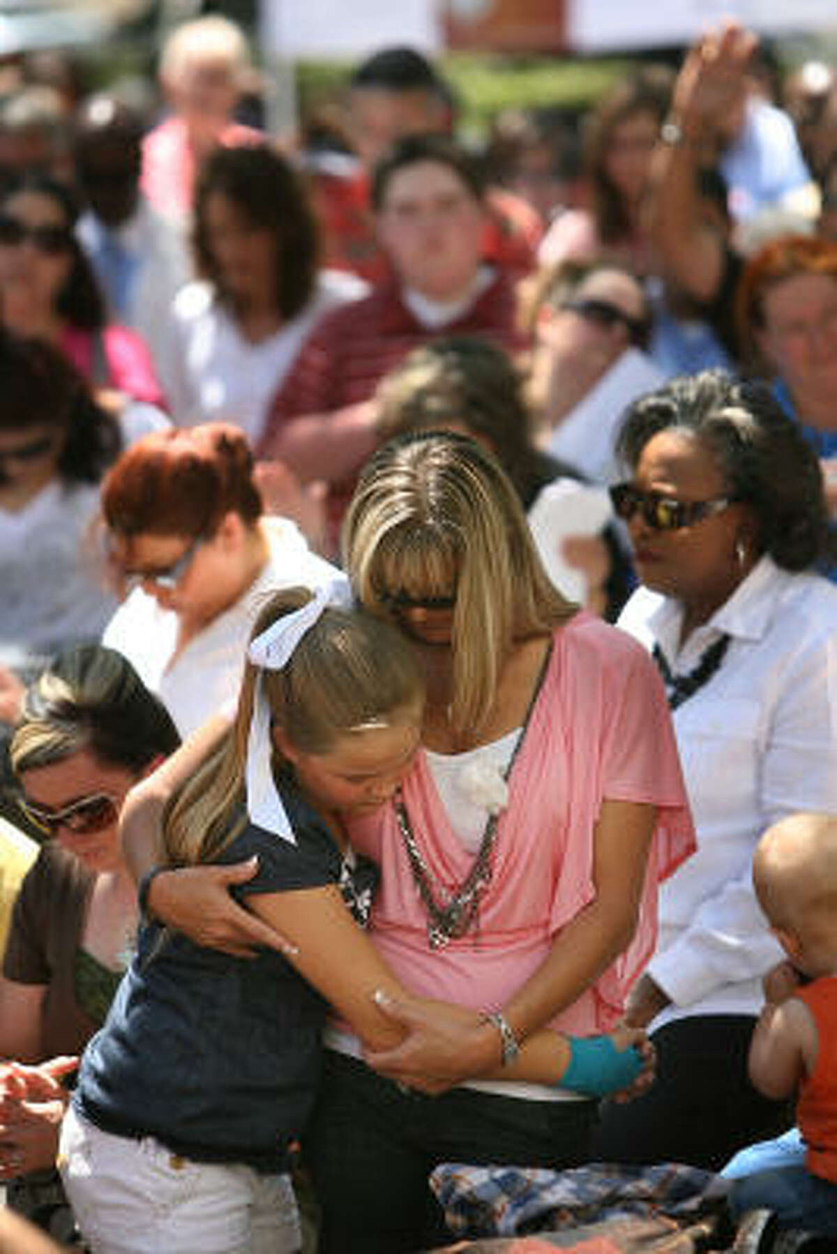 Koral Forline, 10, and mother Tracie Leflet embrace while praying for families to stay together during the