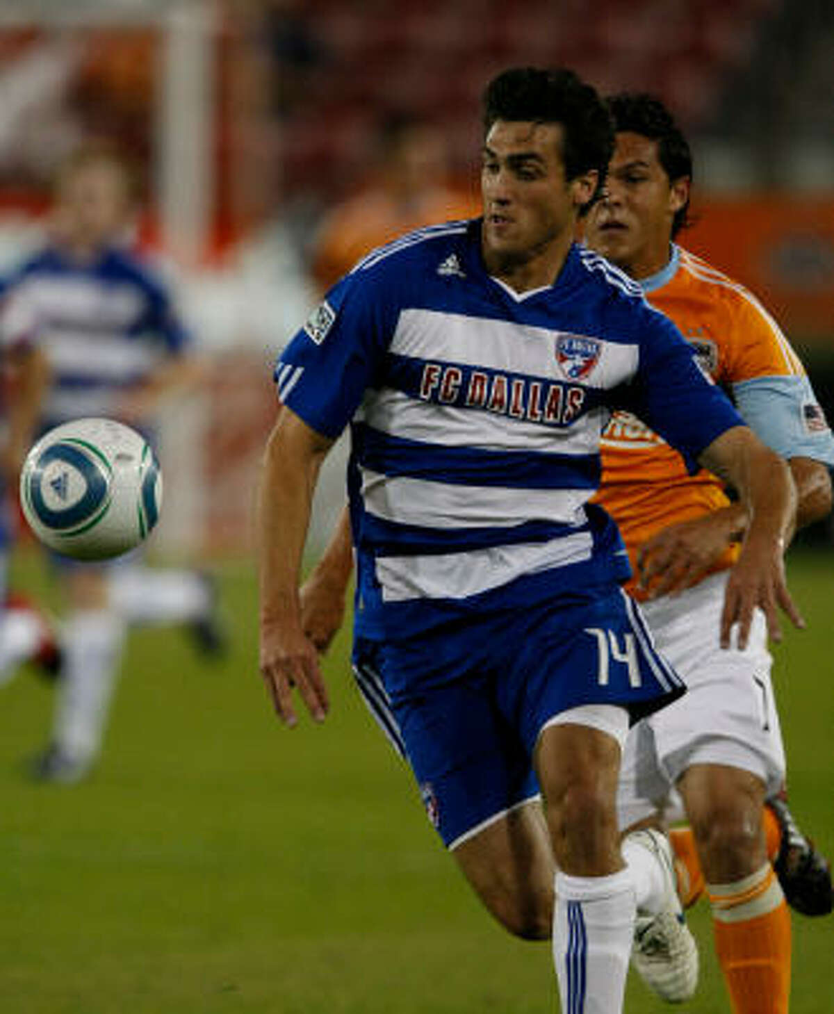 FC Dallas midfielder George John tries to keep control of the ball as Dynamo forward Luis Angel Landin persecutes in the first half.