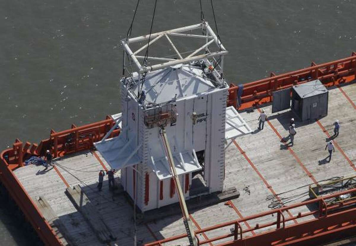 A containment dome made for the leak created by the recent collapse of the Deepwater Horizon oil rig is loaded by crane on to a ship, at the Port of Fourchon, La., Wednesday, May 5, 2010.