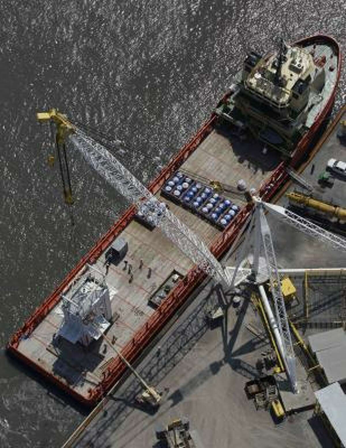 A containment dome, left, made for the leak created by the recent collapse of the Deepwater Horizon oil rig is loaded by crane on to a ship, at the Port of Fourchon, La., Wednesday, May 5, 2010.